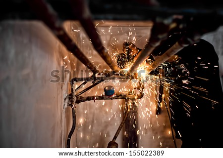 Professional welder working and grinding on pipes - stock photo
