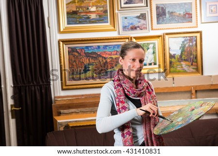 Professional woman artist painting in a studio holding a colorful artists palette and paintbrush in her hand - stock photo
