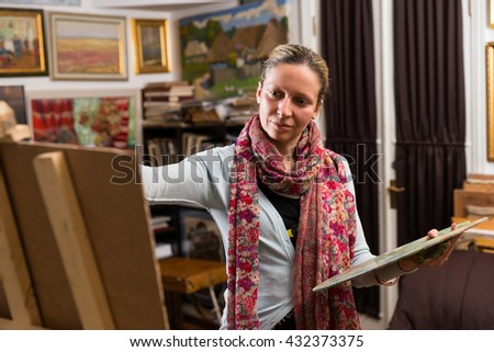 Professional woman artist painting in her studio standing daubing oil paint onto a canvas against a background of original artworks hanging on the wall - stock photo