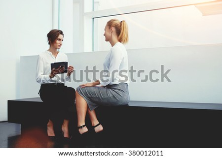 Professional woman employer holding digital tablet in hands while conducting interview with new worker, female managing director with touch pad listening her partner while sitting in office interior