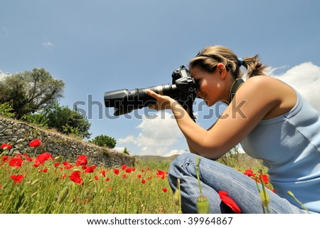 professional woman photographer in a field with poppies in spring - stock photo