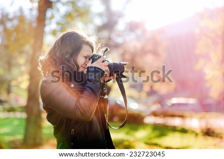 Professional woman photographer taking outdoor portraits with prime lens at sunset, during a sunny day - stock photo
