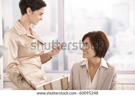 Professional women in discussion in office, working with documents, smiling.?