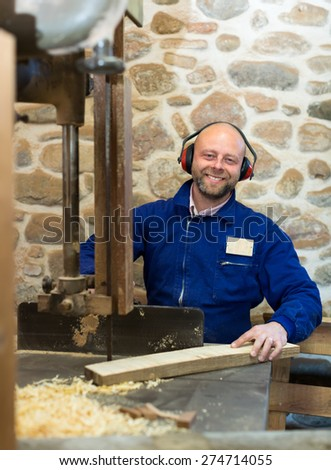 Professional woodworker wearing protective gear and blue uniform is cutting a plank of wood with an industrial fret-saw - stock photo