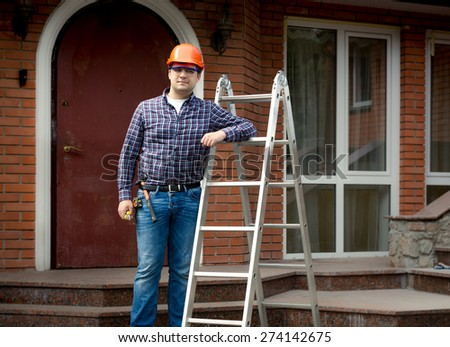 Professional worker posing with metal ladder against building house - stock photo