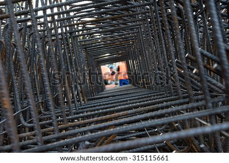 Professional workers wearing uniforms and helmets seen through steel bars reinforcement on a construction site.  - stock photo