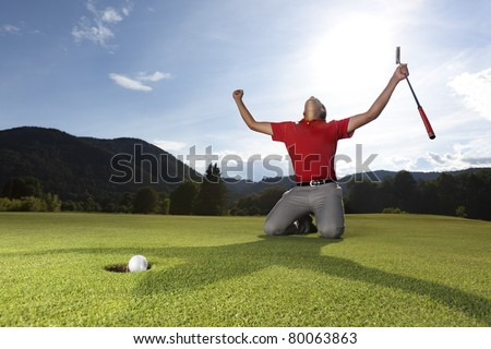 Professional young male golf player on knees and arms raised with putter in hand on golf green being overjoyed as golf ball drops into cup. - stock photo