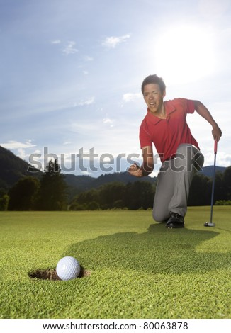 Professional young male golfer with putter in hand on golf green cheering as golf ball drops into cup.
