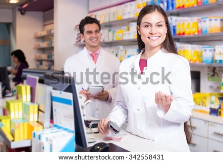 Professional young pharmaceutists at reception of drugstore ready to help - stock photo