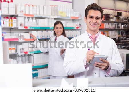 Professional young spanish pharmaceutists at reception of drugstore ready to help - stock photo