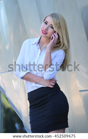 Professional young woman making a business call on mobile phone in the city - stock photo