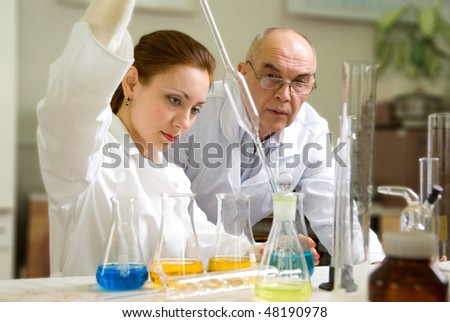 professor and his assistant in the chemical laboratory conducting experiments