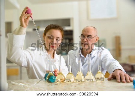 professor and his assistant in the chemical laboratory conducting experiments - stock photo