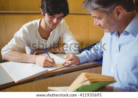 Professor assisting a student with his study in classroom - stock photo