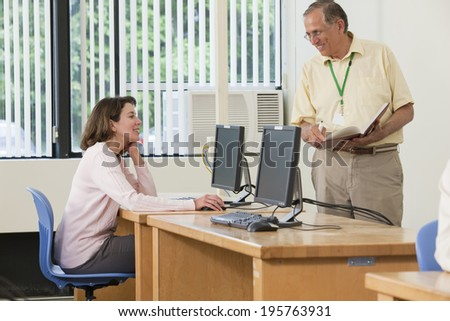 Professor discussing lecture notes with sitting college engineering student - stock photo