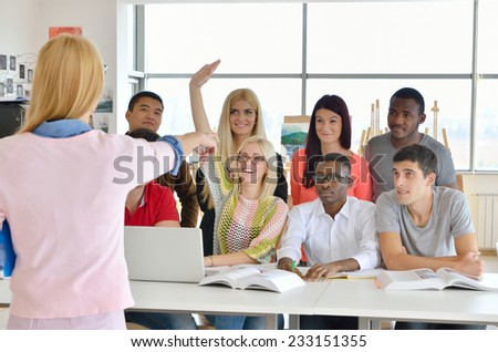 Professor examines a group of young students, black, white, Chinese and girls, hands up - stock photo