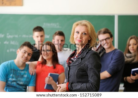 Professor standing in front of a group of students - stock photo