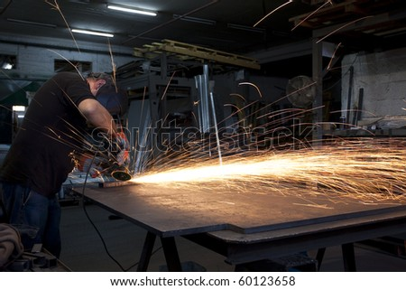 proffesional heavy industry worker with all the safety equipment grinding metal with flying sparks all arround - stock photo