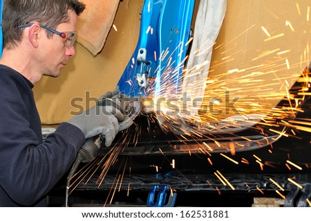 Proffesional worker grinding car body. - stock photo