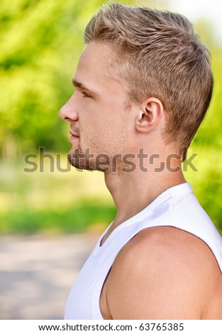 Profile face of young man smiles against summer park.