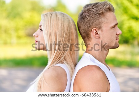 Profile face of young smiling couple against summer park. - stock photo