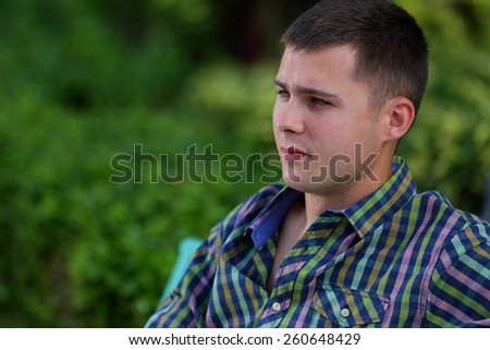 Profile image of a handsome Russian man sitting on a bench - stock photo