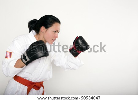 Profile of a beautiful woman in an athletic boxing/fighting stance. - stock photo