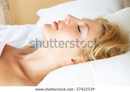 profile of a beautiful young blond woman sleeping peacefully in her bed at home