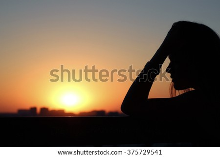 Profile of a beautiful young girl in meditations and reflections at sunset - stock photo