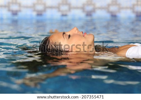 Profile of a beauty relaxed woman face floating in water of a pool enjoying vacations            - stock photo