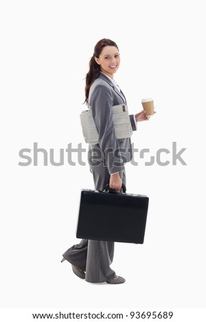 Profile of a businesswoman smiling, walking with a briefcase, with a newspaper under her arm and holding coffee against white background - stock photo