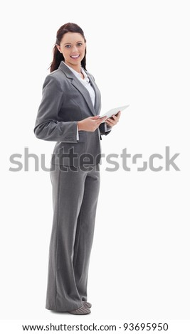 Profile of a businesswoman smiling with a touch pad against white background - stock photo