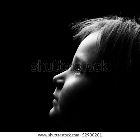 Profile of a child's face with high contrast light - stock photo
