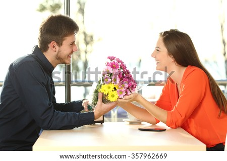 Profile of a couple dating and looking each other with a man giving a bouquet of flowers to his partner in a coffee shop - stock photo