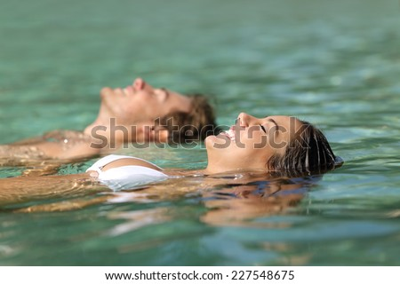 Profile of a couple of tourists swimming in the sea of a tropical resort floating on the turquoise water on summer vacations - stock photo