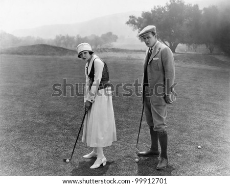 Profile of a couple playing golf in a golf course - stock photo