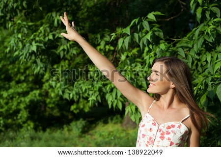 Profile of a girl trying to reach something with stretch hand - stock photo