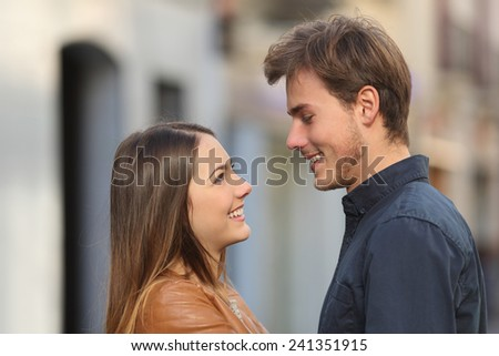 Profile of a happy couple looking each other affectionate in the street - stock photo