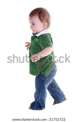 Profile of a little boy wearing a green top and jeans running around. - stock photo