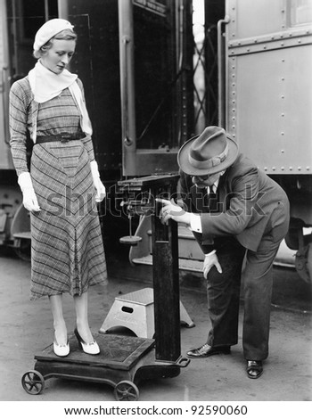 Profile of a man measuring weight of a woman standing on a weighing scale in front of a train - stock photo