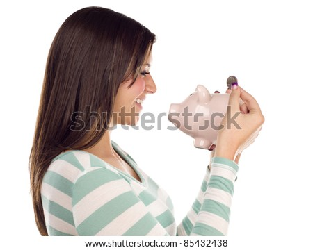 Profile of a Pretty Smiling Ethnic Female Putting a Coin Into Her Pink Piggy Bank Isolated on a White Background.