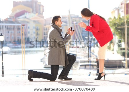 Profile of a proposal of a full body of a fashion elegant couple with a man asking marry to his girlfriend in an idyllic port of an urbanization - stock photo