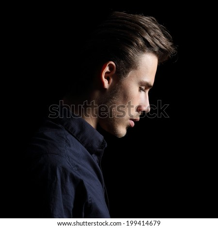 Profile of a sad man face crestfallen on black isolated on a black background        - stock photo