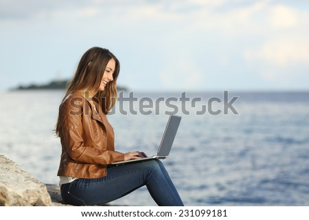 Profile of a self employed woman working with a laptop on the beach with the sea in the background - stock photo