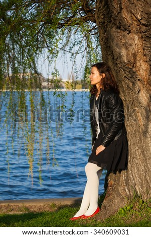 Profile of a serene dreamy woman standing near a tree in a park and looking away - stock photo