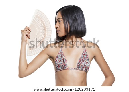 Profile of a young beautiful woman in bikini holding a fan in front.white background. - stock photo