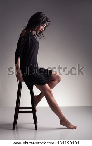 profile of a young brunette model with barefoot looking down on grey background - stock photo