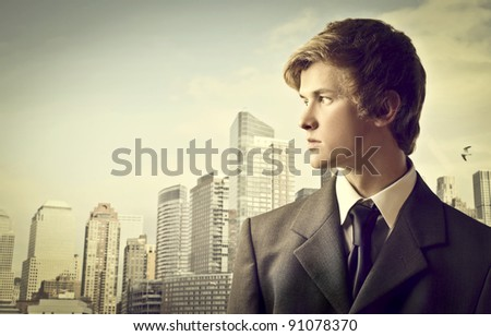 Profile of a young businessman with cityscape in the background - stock photo
