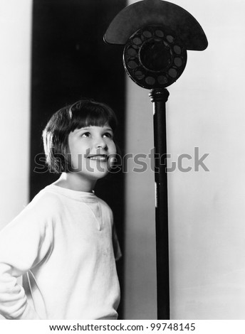 Profile of a young girl looking at a microphone and smiling - stock photo