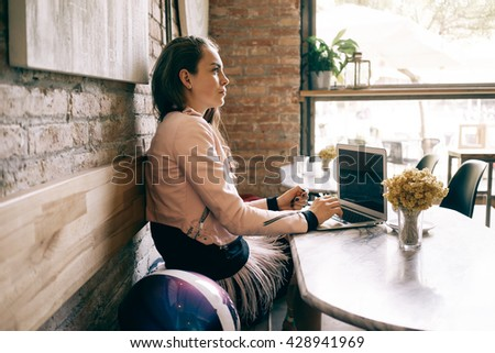 Profile of a young girl sitting with a laptop beside the brick wall in a cafe. Charming woman with a portable computer in a brick interior restaurant is looking forward. - stock photo